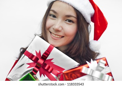 Portrait of young beautiful woman in santa claus hat with christmas gift boxes with ribbons.