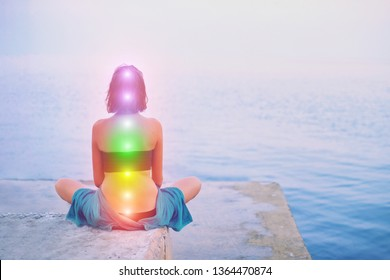Portrait of young beautiful woman sits in a pose of half lotus practicing yoga meditation at blue summer sea environment glowing all seven chakra Kundalini energy exercise Back view Inner mind consept