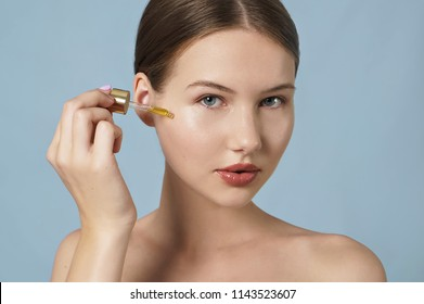 portrait of young beautiful woman with skin care product on blue background