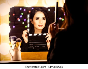 portrait of young beautiful woman with slapstick looking in the mirror