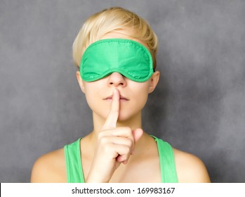 portrait of young beautiful woman in sleep mask making hush sign