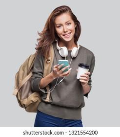 スマートフォンを持つ若い美しい女性。旅行に行く笑顔の学生少女。グレイの背景に分離型