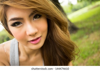 Portrait of young beautiful woman smiling in the park