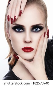 Portrait of young beautiful woman with smoky eyes and long nails over white background