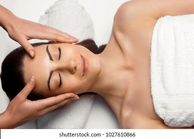 Portrait of Young Beautiful Woman in Spa Salon.Spa Body Massage Treatment and Skincare.Leisure. Face Massage.Facial treatment. Cosmetology