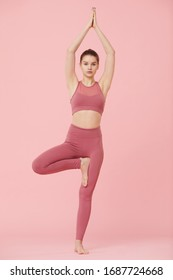 Portrait of young beautiful woman standing in yoga pose isolated on pink background