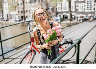 Portrait of a young beautiful woman standing with bouguet of pink tulips on the bridge in Amsterdam old city