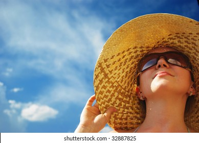Portrait of young beautiful woman in straw hat and sunglasses