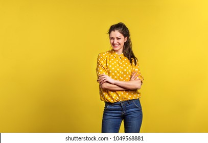 Portrait of a young beautiful woman in studio on yellow background.