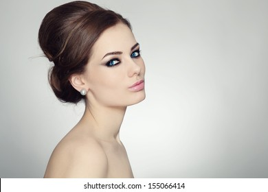 Portrait of young beautiful woman with stylish make-up and hair bun