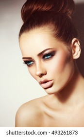 Portrait of young beautiful woman with stylish hair bun and smoky eye make-up