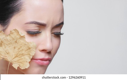 Portrait of young beautiful woman suffering the dryness on skin, holds dry leaf. Moisturizing, problem skin, rejuvenation, dehydration, skincare, beauty, collagen, vitamins, treatment, therapy concept