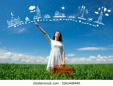 portrait of young beautiful woman with suitcase in the field and abstract travel map in air