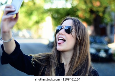 Portrait of a young beautiful woman taking selfie with her smartphone. Outdoors.