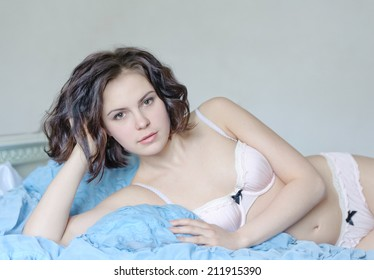 Portrait of young beautiful woman in underwear lying on a bed