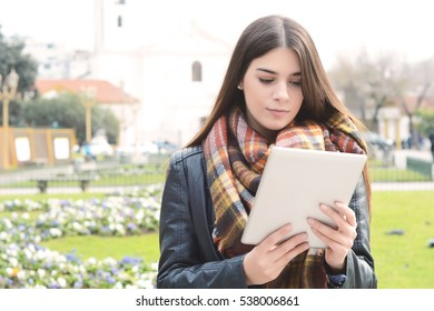 Portrait of a young beautiful woman using her tablet. Outdoors.