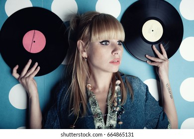 Portrait of a young beautiful woman with vinyl records in hands
