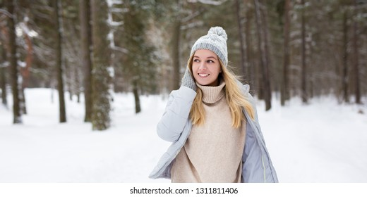portrait of young beautiful woman walking in winter forest