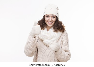 Portrait of young beautiful woman in warm accessories shows thumbs up like a sign of ready for spring. Isolated on white background.
