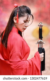 portrait of young and beautiful woman wearing red chinese warrior costume with black sword, she post using sword among green trees and nature outdoor
