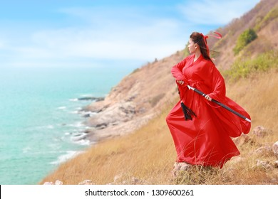 portrait of young and beautiful woman wearing red chinese warrior costume with black sword, she post using sword on moutain with sea and nature outdoor