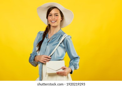portrait of young and beautiful woman wearing a light blue shirt and a white hat