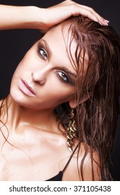 Portrait of young beautiful woman with wet shining  makeup  on black background