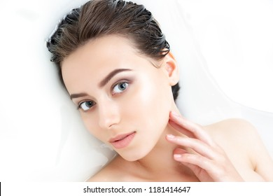 Portrait of young beauty Caucasian female woman adult with clean pure skin taking spa relaxing in bath with white soap shampoo water. Skin beauty health care concept. Body part bare shoulder