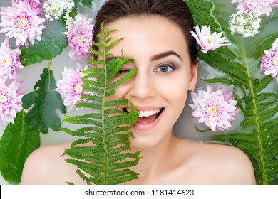 Portrait of young beauty female woman smiling with clean pure skin taking spa relaxing in bath with flowers and green leafs white soap water. Skin beauty health care concept. Body part and nature