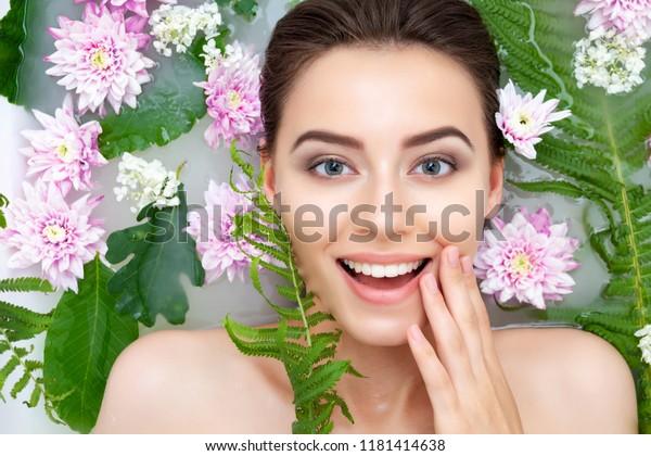 Porträt von jungen Schönheitsweibchen lächeln mit sauberer reiner Haut, die Spa entspannend im Bad mit Blumen und grünen Blättern weißes Seifenwasser. Konzept der Hautbeauty-Gesundheitsversorgung. Körperteil und Natur