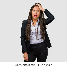 Portrait of a young black business woman worried and overwhelmed, forgetful, realize something, expression of shock at having made a mistake