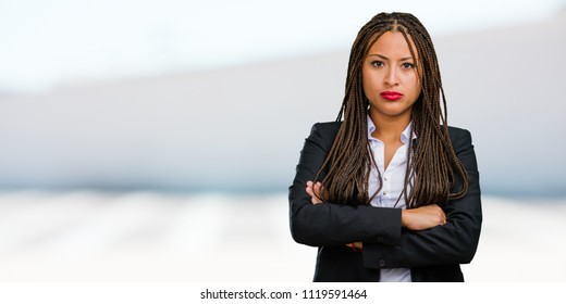 Portrait of a young black business woman very angry and upset, very tense, screaming furious, negative and crazy