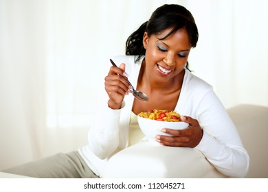 Portrait of a young black female having healthy breakfast while is sitting on couch at home indoor. with copyspace
