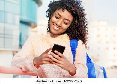 Portrait of young black girl using phone