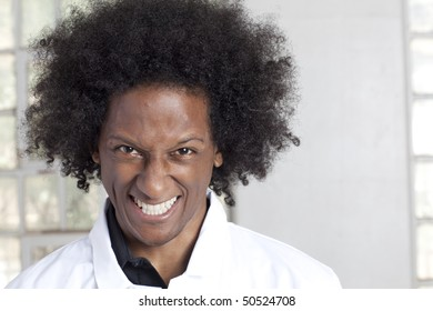 Portrait of a young black man with an afro and a lab coat grinning crazily at the camera. Horizontal format.