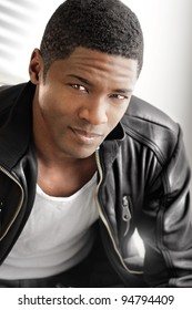 Portrait of a young black man in leather jacket against modern bright background