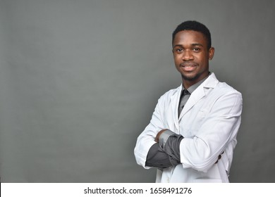 portrait of a young black man in medical field, wearing a white coat smiling