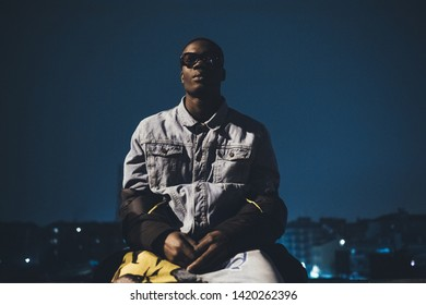 portrait of young black man posing outdoor and looking straight – youth culture, imaginative, freedom
