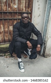 portrait of young black man sitting in the street and looking camera– originality, youth, pensive
