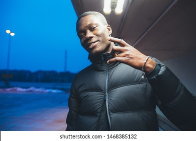 portrait of young black man standing outdoor gesture with hand looking the camera – imaginative, youth, originality