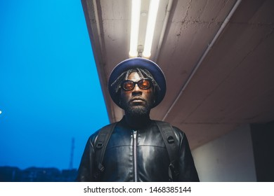 portrait of young black man standing outdoor and looking camera – new generation, youth, originality