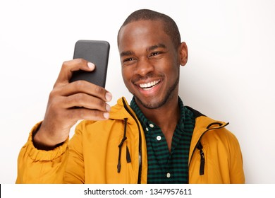 Portrait of young black man taking selfie with cellphone against isolated white background
