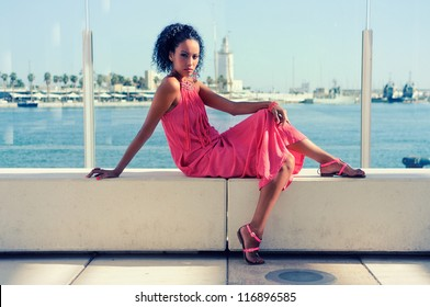 Portrait of a young black woman, afro hairstyle, wearing long pink dress, in the harbor