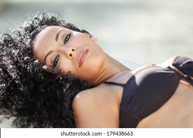 Portrait of a young black woman, afro hairstyle, wearing bikini