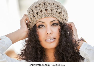 Portrait of a young black woman, afro hairstyle, in urban background, girl wearing wool cap