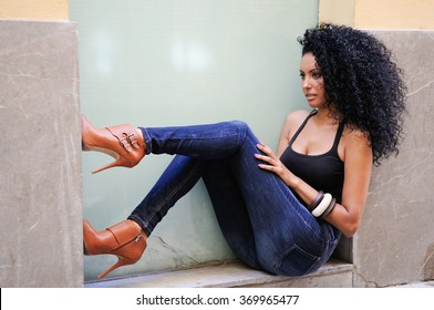 Portrait of a young black woman, afro hairstyle, wearing blue jeans in urban background