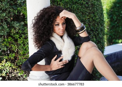 Portrait of a young black woman, afro hairstyle, in urban background. Girl with elegant clothes and bracelet.