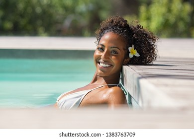 Portrait of young black woman in bikini in spa swimming pool looking at camera. Beautiful african girl with enjoying vacation at resort pool. Happy healthy lady leaning the head at poolside outdoor.