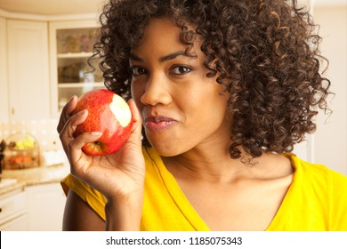 Portrait of young black woman eating fresh red apple inside house kitchen