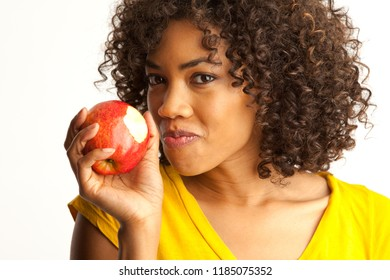 Portrait of young black woman eating fresh red apple isolated on white